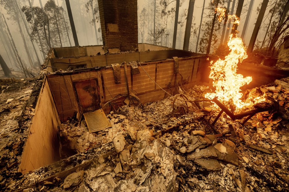Flames burn at a home leveled by the Creek Fire along Highway 168 on Tuesday, Sept. 8, 2020, in Fresno County, Calif. (AP Photo/Noah Berger)