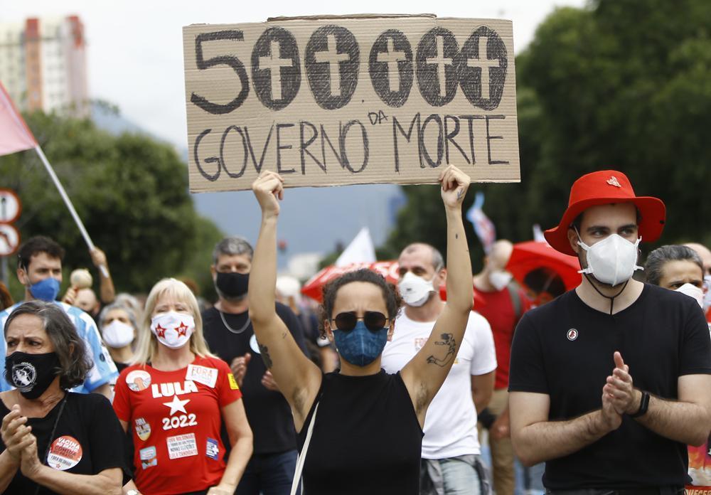 """Eine Frau, die eine schützende Gesichtsmaske trägt, hält ein Schild mit einer Nachricht auf Portugiesisch;  """"500.000, Regierung des Todes"""" während eines Protests gegen den Umgang des brasilianischen Präsidenten Jair Bolsonaro mit der Coronavirus-Pandemie und die Wirtschaftspolitik, von der sie sagen, dass sie den Interessen der Armen und der Arbeiterklasse schadet, in Rio de Janeiro, Brasilien, Samstag, 19. Juni 2021. Brasilien nähert sich einer offiziellen COVID-19-Todesrate von 500.000 – der zweithöchsten der Welt.  (AP-Foto/Bruna Prado)"""
