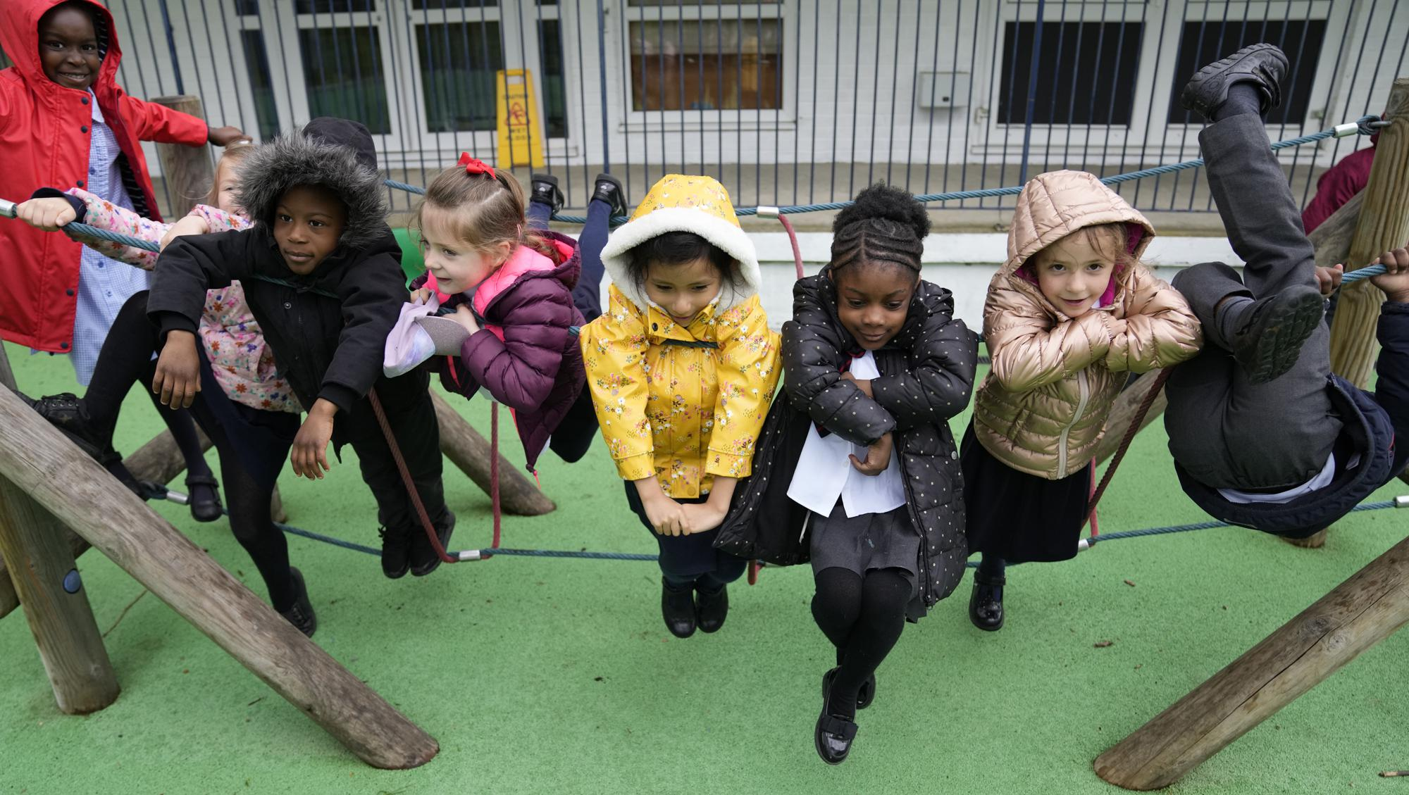 Faith, left, with some of her fellow pupils Julia, Nana, Yaw, Alexandra, Leandra, and Amariah, right play on a rope swing at the Holy Family Catholic Primary School during a break, in Greenwich, London, Wednesday, May 19, 2021. Holy Family, like schools across Britain, is racing to offset the disruption caused by COVID-19, which has hit kids from low-income and ethnic minority families hardest. (AP Photo/Alastair Grant)