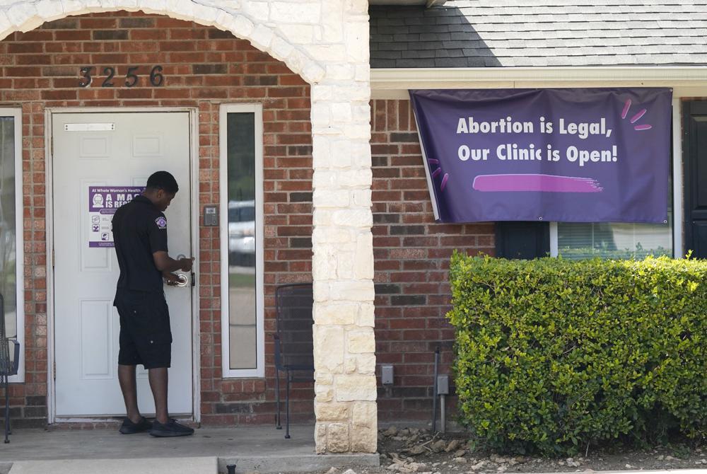 Un guardia de seguridad abre la puerta de la clínica Whole Woman's Health, en Fort Worth, Texas, el miércoles 1 de septiembre de 2021, la cual tiene un letrero que informa al público que está abierta. (AP Foto/LM Otero)