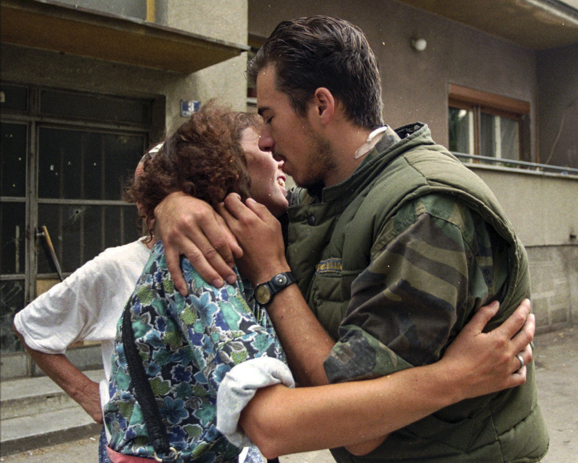 FILE- In this July 19, 1995, file picture, Ahmed Ustic, 19, one of several thousand Bosnian men who took part in the death march from Srebrenica to Tuzla, kisses a friend in Tuzla.  Survivors of the genocide in the eastern Bosnian town of Srebrenica, mainly women, will on Saturday July 11, 2020, commemorate the 25th anniversary of the slaughter of their fathers and brothers, husbands and sons. The slaughter was the only atrocity of the brutal war that has been confirmed an act of genocide.(AP Photo/Darko Bandic, File)