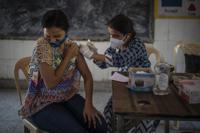 A woman reacts as a health worker inoculates her during a vaccination drive against coronavirus inside a school in New Delhi, India, Wednesday, Oct. 20, 2021. India is nearing a milestone of administering a total of one billion doses against COVID-19. (AP Photo/Altaf Qadri)