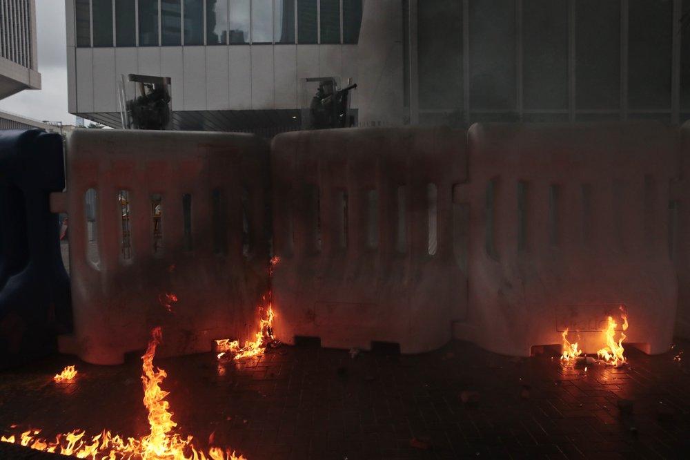 Hong Kong protesters build wall, set fire on main street
