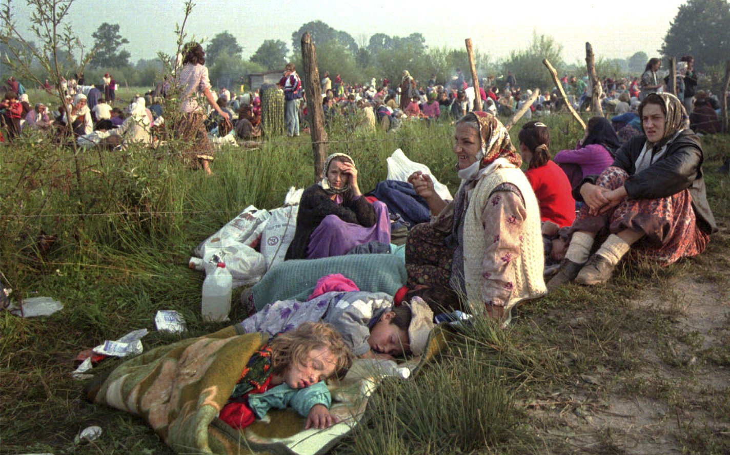 FILE - In this Friday, July 14, 1995, file picture, refugees from Srebrenica who had spent the night in the open air, gather outside the U.N. base at Tuzla airport.  Survivors of the genocide in the eastern Bosnian town of Srebrenica, mainly women, will on Saturday July 11, 2020, commemorate the 25th anniversary of the slaughter of their fathers and brothers, husbands and sons. (AP Photo/Darko Bandic, File)