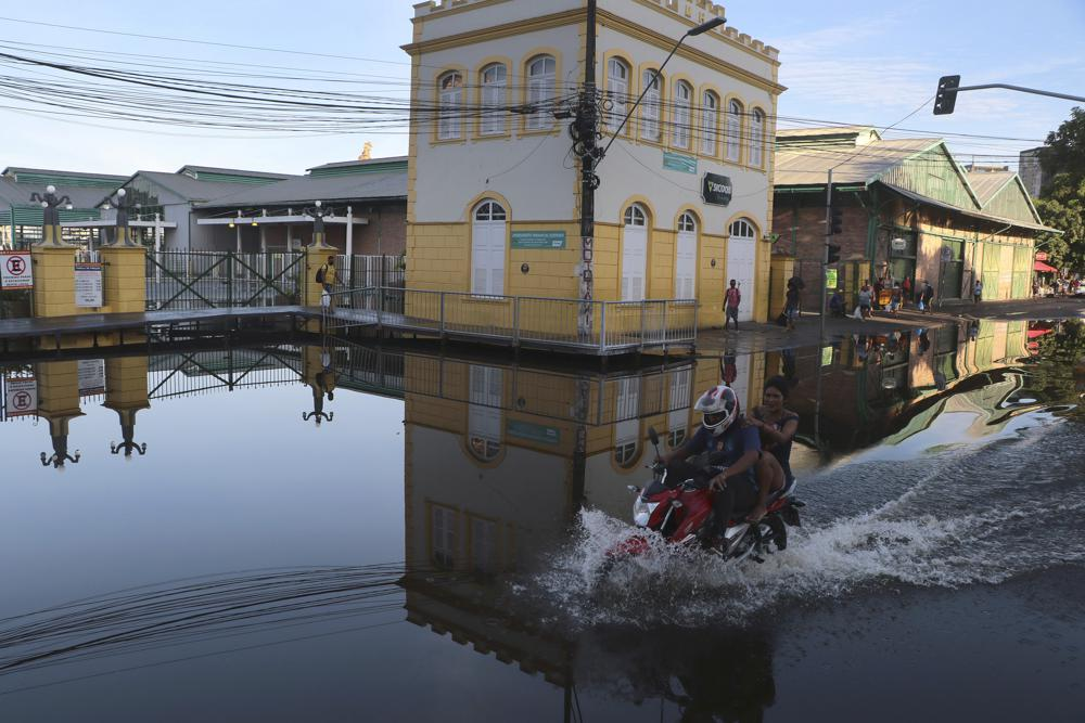 A man rides his motorcycle through a street flooded by the Negro River, in downtown Manaus, Amazonas state, Brazil, Tuesday, June 1, 2021. Rivers around Brazil's biggest city in the Amazon rain forest have swelled to levels unseen in over a century of record-keeping, according to data published Tuesday by Manaus' port authorities. (AP Photo/Edmar Barros)
