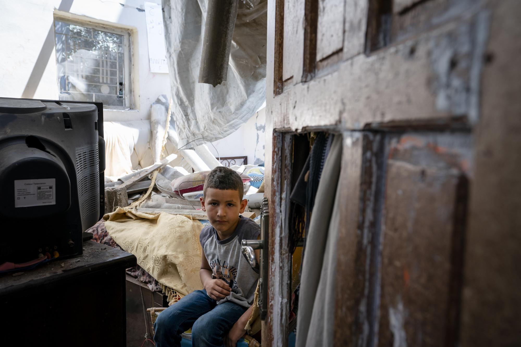 Abu Amsha, 6, sits for a portrait in his bedroom that was damaged when an airstrike destroyed the neighboring building prior to a cease-fire that halted an 11-day war between Gaza's Hamas rulers and Israel, Wednesday, May 26, 2021, in Beit Hanoun, Gaza Strip. (AP Photo/John Minchillo)