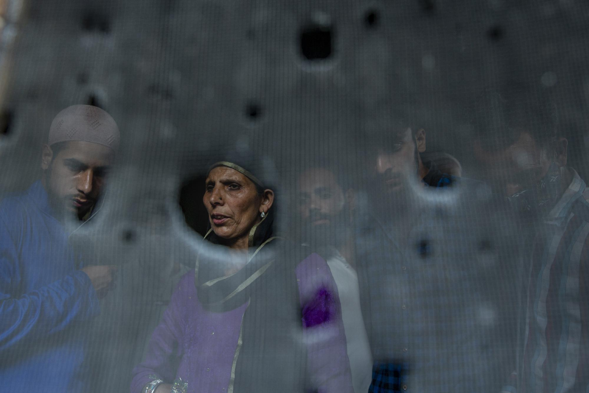 Kashmiri villagers are seen through the bullet ridden iron mesh of a window of a home where suspected rebels were taking refuge, after a gunfight in Pulwama, south of Srinagar, Indian controlled Kashmir, Friday, July 2, 2021. Five suspected rebels and an army soldier were killed in a gunfight in Indian-controlled Kashmir on Friday, officials said, as violence in the disputed region has increased in recent weeks. (AP Photo/ Dar Yasin)