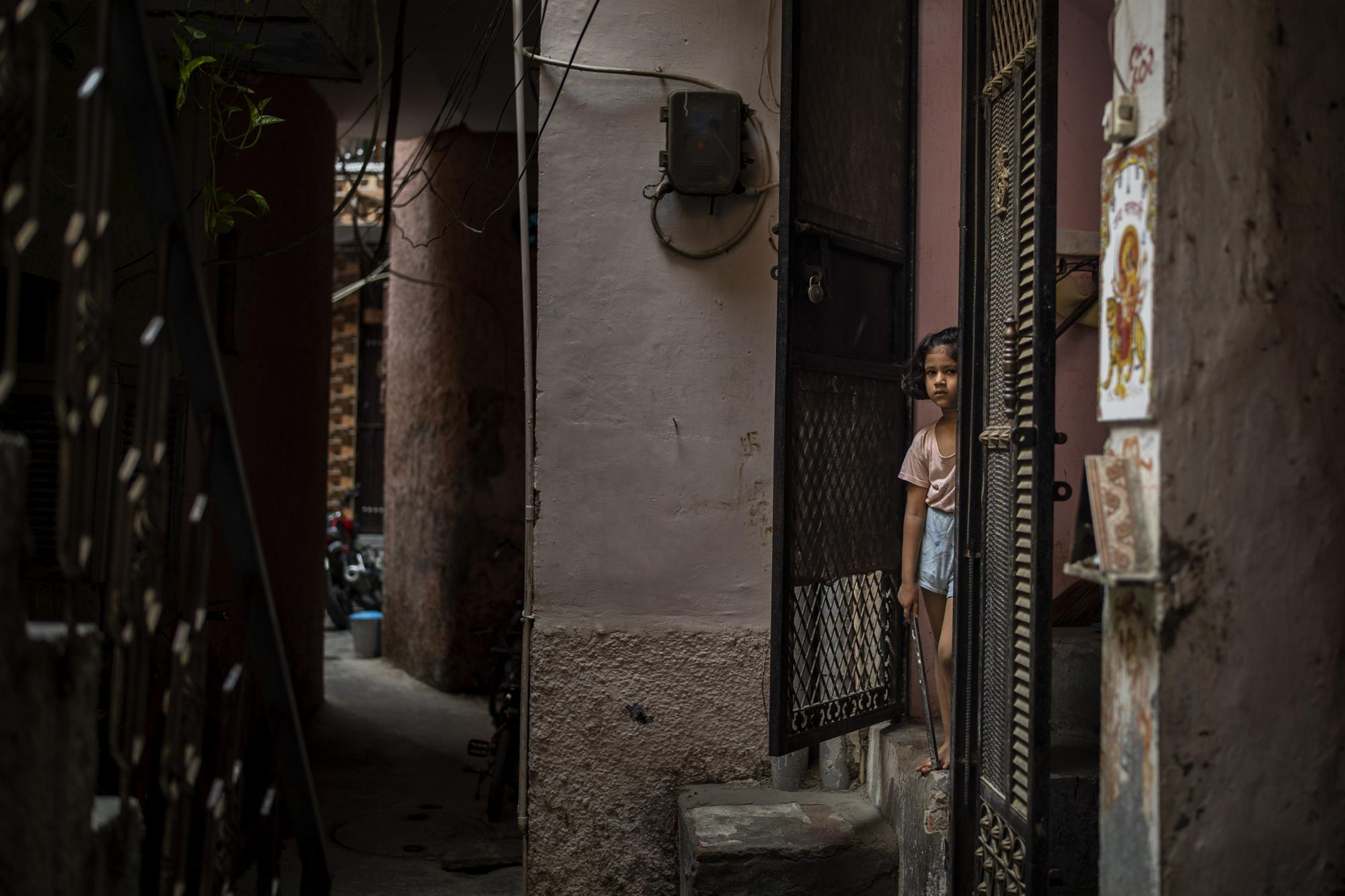A young girl stands at the entrance of her house next to the house of a 9-year-old girl from the lowest rung of India's caste system who, according to her parents and protesters, was raped and killed earlier this week, in New Delhi, India, Thursday, Aug. 5, 2021. Rape and sexual violence have been under the spotlight in India since the 2012 gang rape and killing of a 23-year-old student on a New Delhi bus. The attack sparked massive protests and inspired lawmakers to order the creation of fast-track courts dedicated to rape cases and stiffen penalties for those convicted of the crime. (AP Photo/Altaf Qadri)
