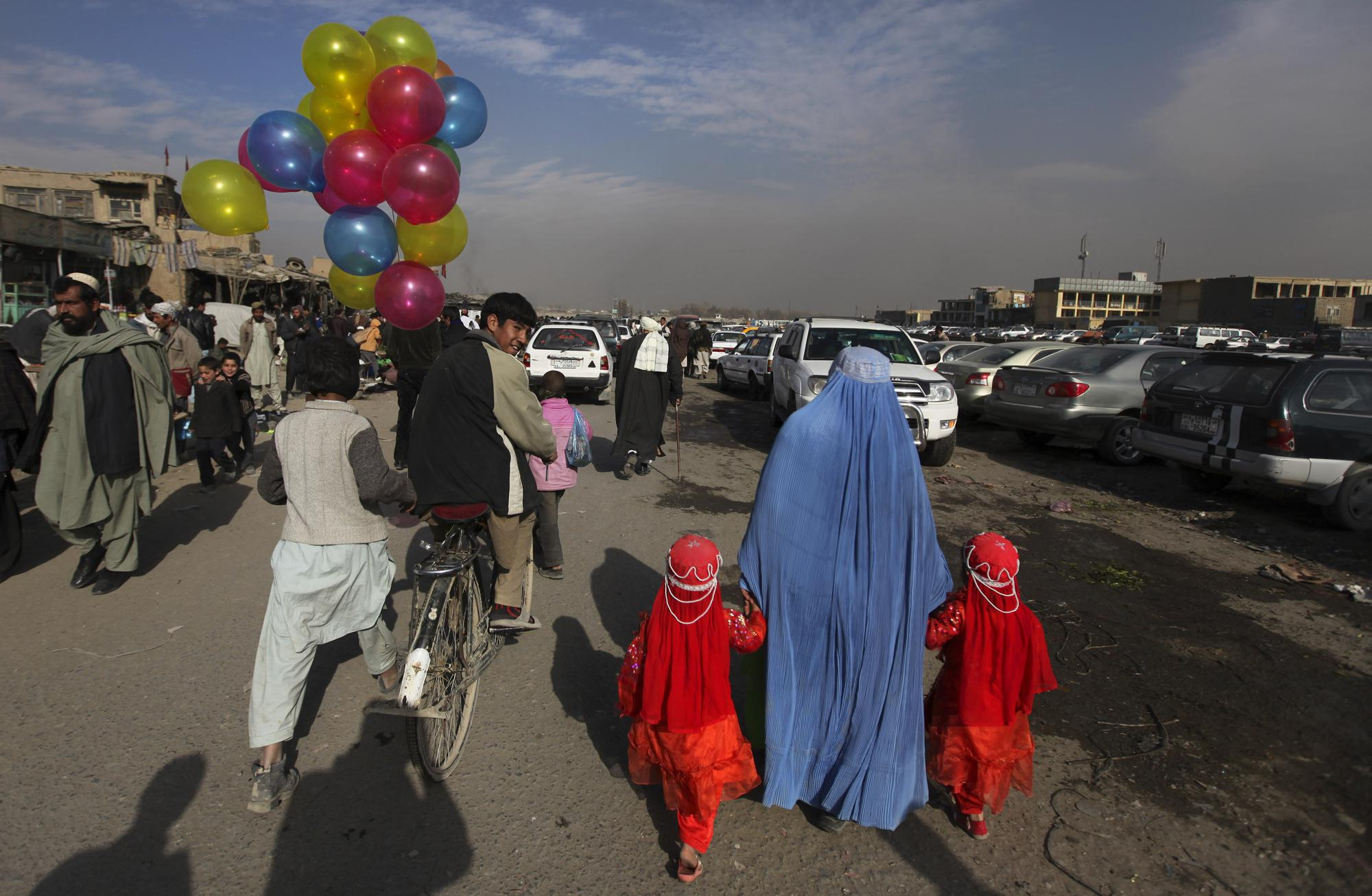 FILE - In this Jan. 3, 2011 file photo, a balloon seller riding a bicycle looks towards a woman holding hands with two young girls at a market in Kabul, Afghanistan. (AP Photo/Altaf Qadri, File)