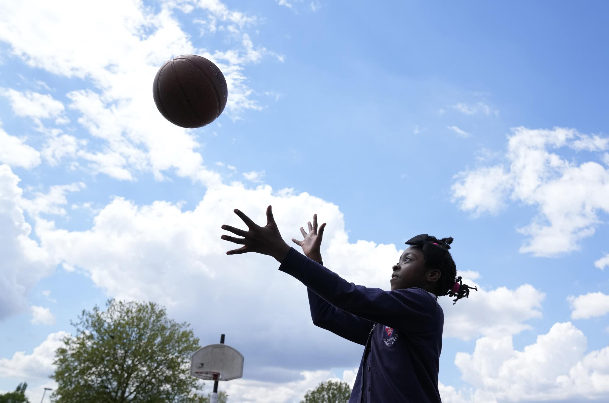Ayomide plays catch in the playground of the Holy Family Catholic Primary School in Greenwich, London, Wednesday, May 19, 2021. (AP Photo/Alastair Grant)