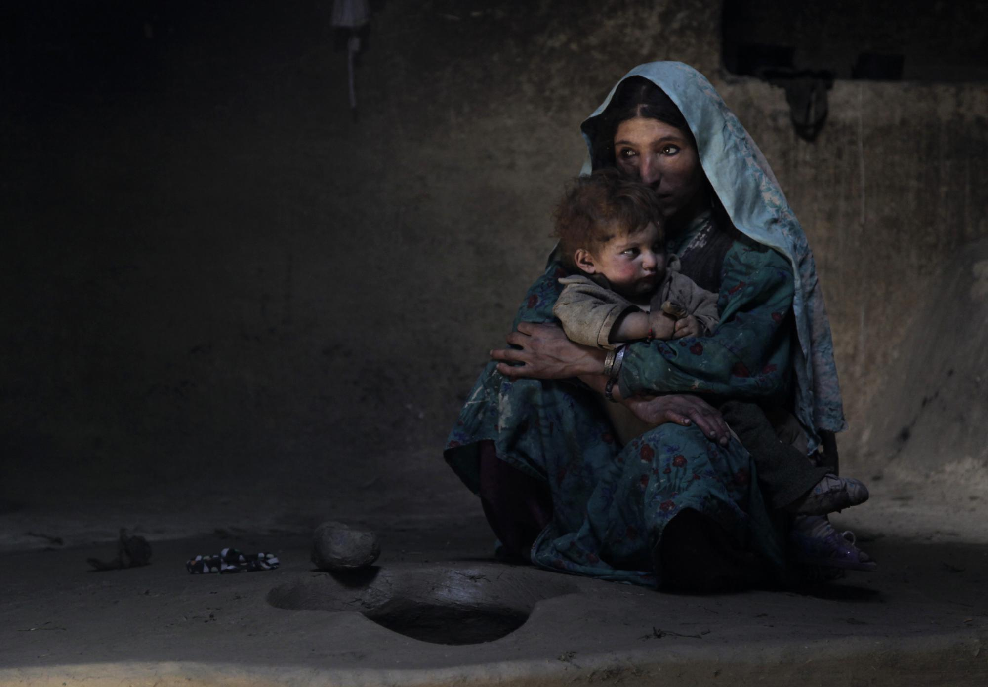 """Sarab village resident Raihan comforts her 1-year-old son after having an early morning opium smoke with family members in the Badakhshan province of Afghanistan, July 13, 2009. Raihan was addicted to opium while pregnant with her son making him an addict at birth. """"When he was born, he would cry day and night. But when she blows smoke in his face, he sleeps,"""" said her father Islam Beg. In dozens of mountain hamlets in this remote corner of Afghanistan, opium addiction has become so entrenched that whole families, from toddlers to old men, are addicts. (AP Photo/Julie Jacobson)"""