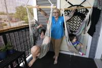 """In this July 28, 2021 photo, Christina Darling plays with her sons Kayden, 10, left, and Brennan, 4, at home in Nashua, N.H. Darling and her family have qualified for the expanded child tax credit, part of President Joe Biden's $1.9 trillion coronavirus relief package. """"Every step closer we get to a livable wage is beneficial. That is money that gets turned around and spent on the betterment of my kids and myself,"""" said Darling, a housing resource coordinator who had been supplementing her $35,000-a-year salary with monthly visits to the Nashua Soup Kitchen and Shelter's food pantry. (AP Photo/Elise Amendola)"""