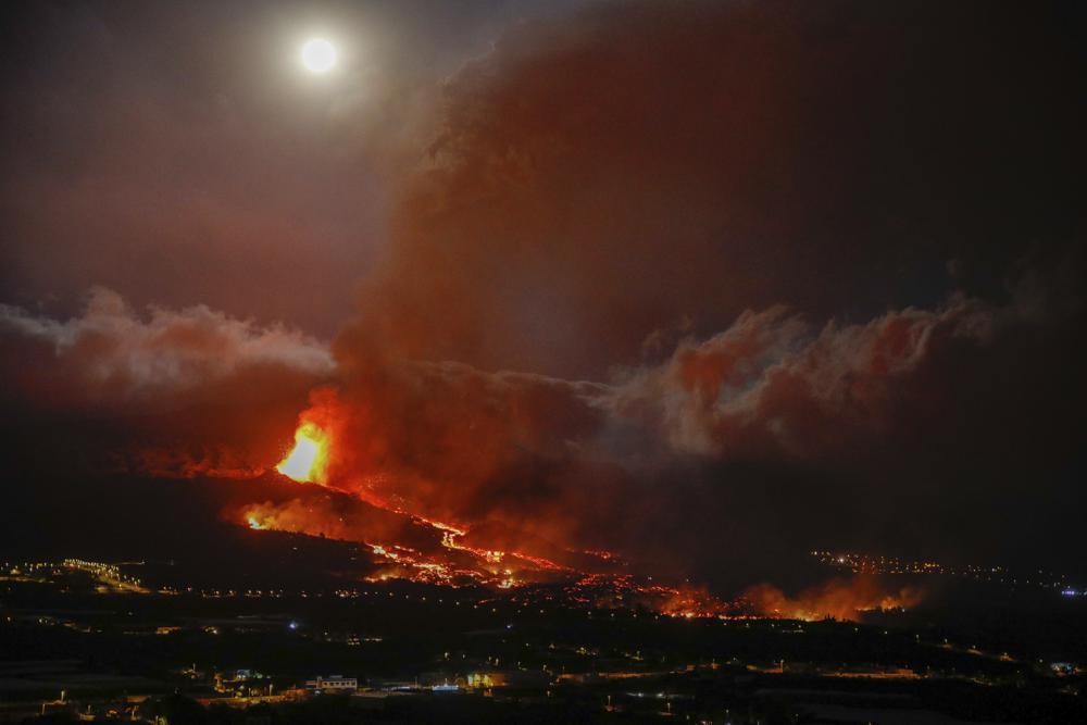 La lava entra en erupción de un volcán cerca de El Paso en la isla de La Palma en las Canarias, España, el lunes 20 de septiembre de 2021. Ríos de lava gigantes caen lenta pero implacablemente hacia el mar después de que un volcán, visto en segundo plano, hizo erupción en un Isla española frente al noroeste de África.  La lava está destruyendo todo a su paso, pero las evacuaciones rápidas ayudaron a evitar víctimas después de la erupción del domingo.  (Kike Rincon, Europa Press vía AP)
