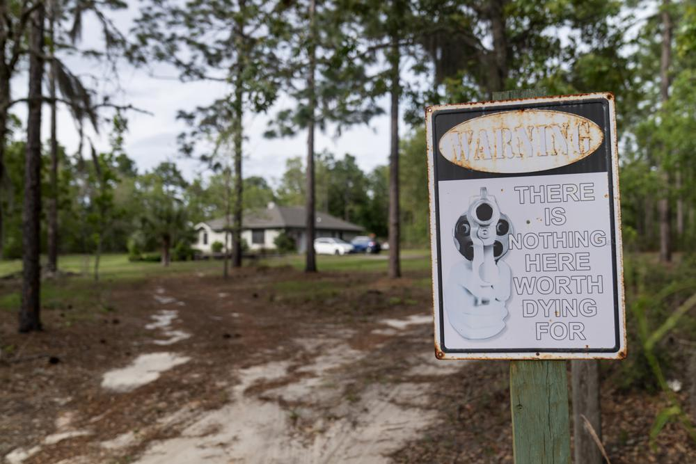 """A sign featuring a pistol barrel pointed at would-be trespassers warns, """"There is Nothing Here Worth Dying For"""" at the former home of Charles Newcomb, in Hawthorne, Fla., Thursday, April 15, 2021. Newcomb, the local KKK chapter's leader, known as the Exalted Cyclops, was involved in a 2015 murder plot against a former inmate at a prison where Newcomb once worked as a guard. (AP Photo/David Goldman)"""