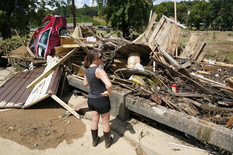 Eine Frau betrachtet Trümmer, die am Sonntag, den 22. August 2021, in Waverly, Tennessee, gegen eine Brücke über einen Bach gespült wurden. Starke Regenfälle führten am Samstag in Middle Tennessee zu Überschwemmungen und haben zu mehreren Todesfällen geführt, als Häuser und Landstraßen weggespült wurden.  (AP Foto/Mark Humphrey)