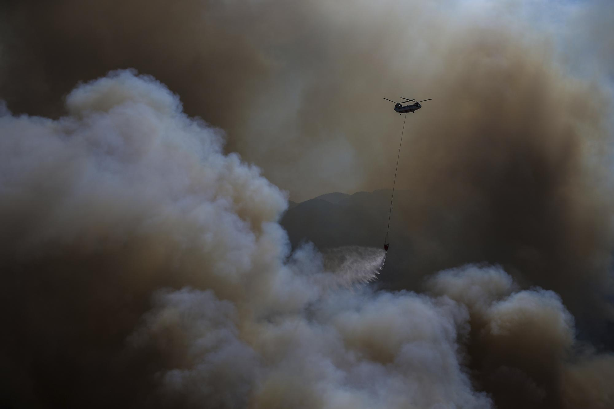 A helicopter drops water over a wildfire in Koycegiz, Mugla, Turkey, Monday, Aug. 9, 2021. (AP Photo/Emre Tazegul)