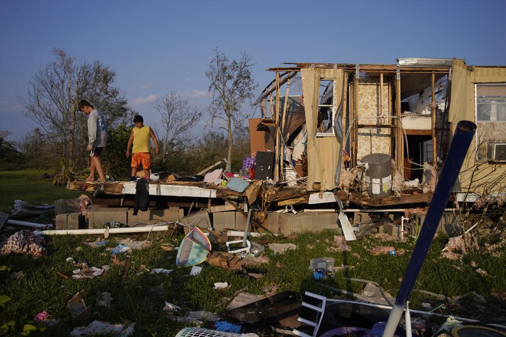 ARCHIVO - En esta fotografía de archivo del 4 de septiembre de 2021, Aiden Locobon, izquierda, y Rogelio Paredes miran a través de los restos de la casa de su familia destruida por el huracán Ida en Dulac, Luisiana, estudiantes de Luisiana, que regresaron a clase después de un año y un la mitad de las interrupciones de COVID-19 mantuvieron a muchos de ellos en casa, ahora vuelven a faltar a la escuela después del huracán Ida.  Un cuarto de millón de estudiantes de escuelas públicas en todo el estado no tienen una escuela a la que reportarse, aunque los mejores educadores prometen que el regreso está, como mucho, en unas semanas, no en meses.  (Foto AP / John Locher, archivo)