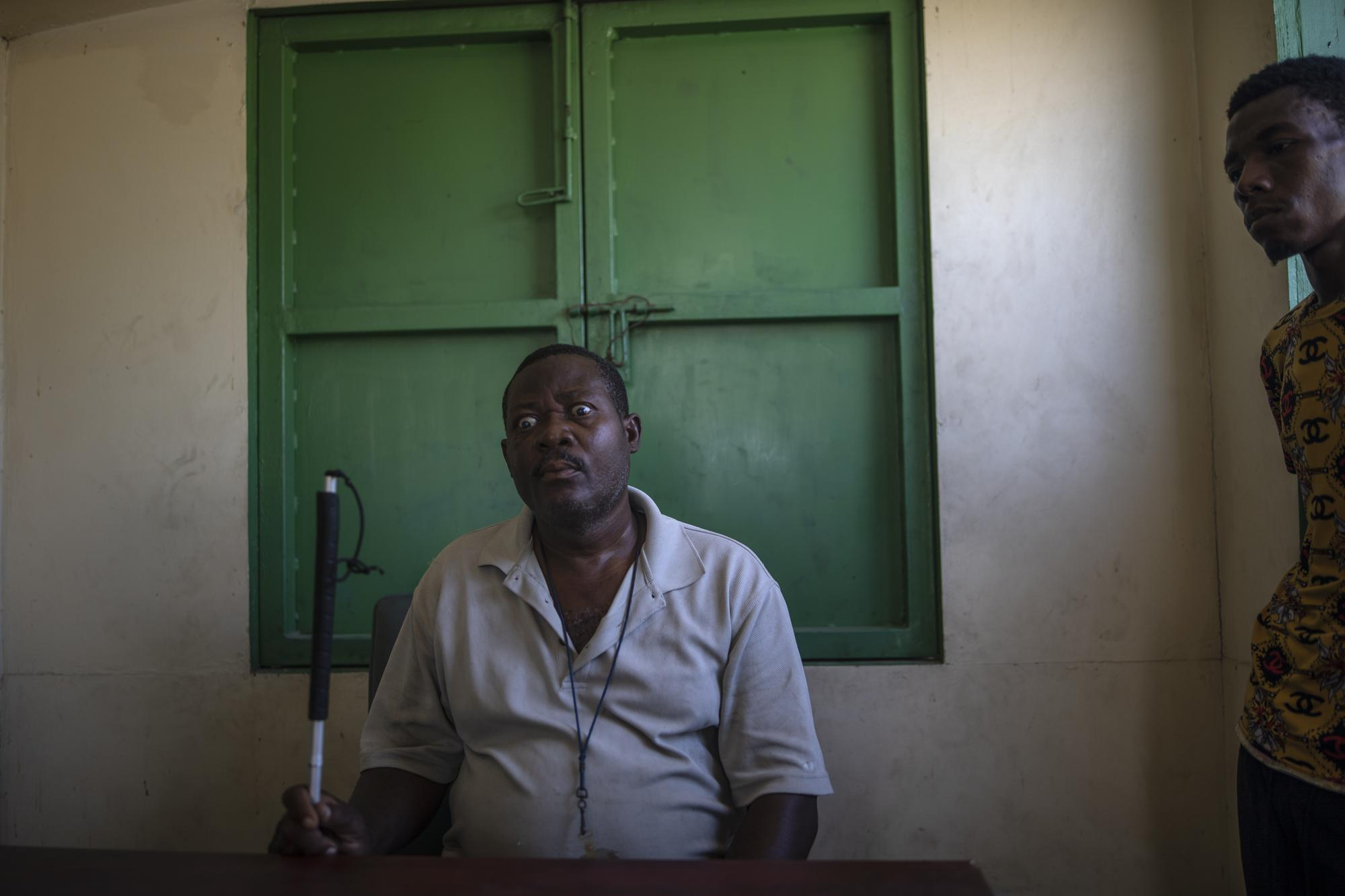 """Leader La Piste's displaced residents, Joseph Dieu Faite, who is visually impaired, recalls the assault lead by police in June, at a shelter for the internally displaced in Port-au-Prince, Haiti, Friday, Sept. 17, 2021. """"There were some gangsters there, I have to acknowledge that, but the police did not ask, did not say a word, did not make a difference, just evicted us and then took matches and gasoline and burned our houses one by one,"""" Faite said. (AP Photo/Rodrigo Abd)"""