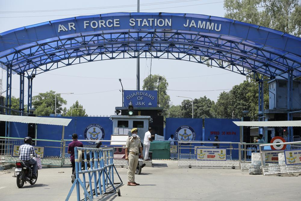 A police officer stands outside the Jammu air force station after two suspected blasts were reported early morning in Jammu, India, Sunday, June 27, 2021. Indian officials said Sunday they suspected explosives-laden drones were used to attack the air base in the disputed region of Kashmir, calling it the first such incident of its kind in India.