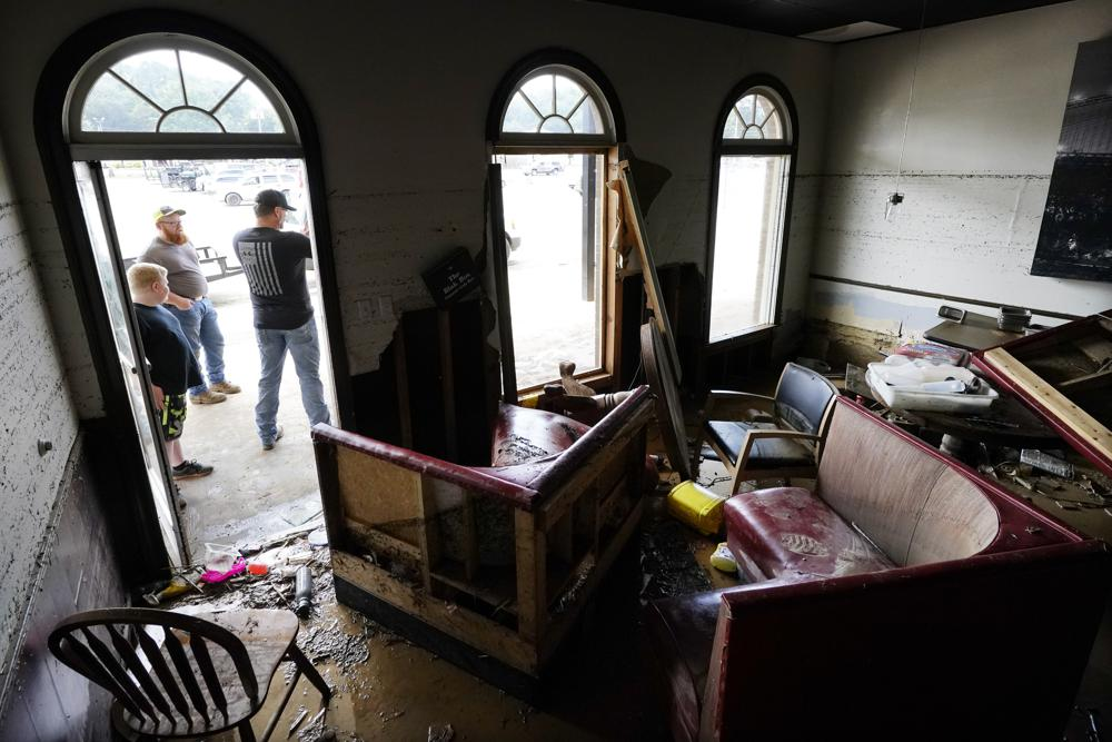 Kansas Klein, standing at right in the doorway, talks outside of his destroyed Bella Blak Pizzeria restaurant, Sunday, Aug. 22, 2021, in Waverly, Tenn. Heavy rains caused flooding in Middle Tennessee and have resulted in multiple deaths as homes and rural roads were washed away. (AP Photo/Mark Humphrey)