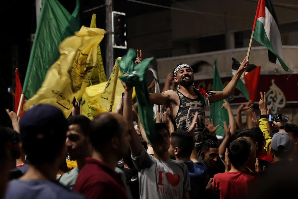 Palestinians dance as they wave green Hamas and their national flags while celebrating the cease-fire agreement between Israel and Hamas in Gaza City, early Friday, May 21, 2021. (AP Photo/Adel Hana)