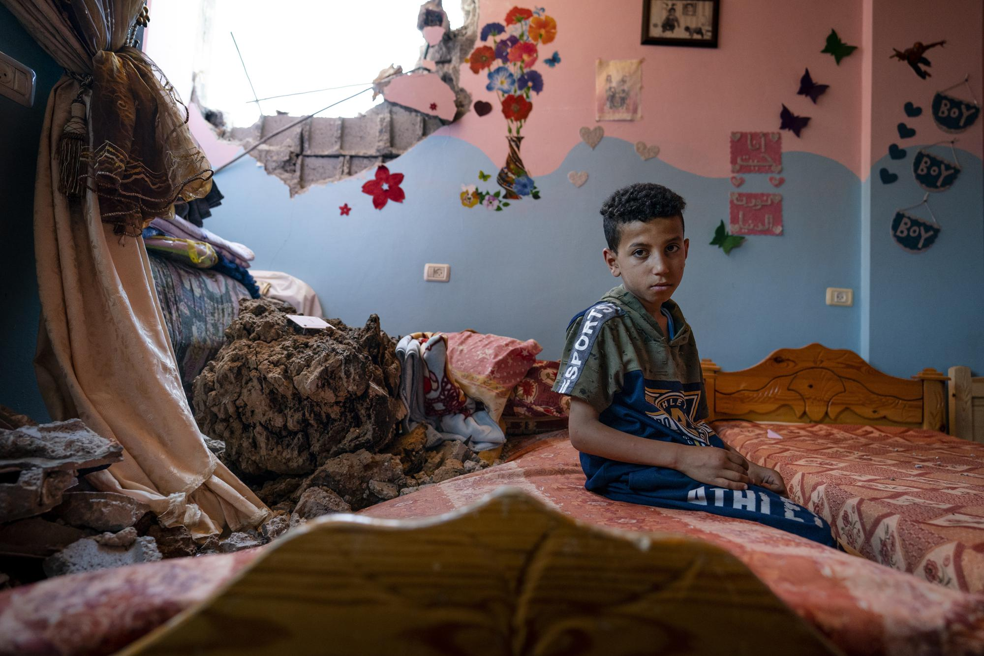 Ibrahim Al-Masri, 10, sits for a portrait in his bedroom that was damaged when an airstrike destroyed the neighboring building prior to a cease-fire that halted an 11-day war between Gaza's Hamas rulers and Israel, Wednesday, May 26, 2021, in Beit Hanoun, Gaza Strip. (AP Photo/John Minchillo)