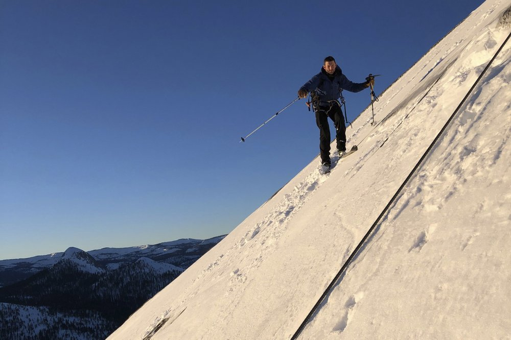2 skiers carve their way in crusty snow in descent of Half Dome at Yosemite National Park