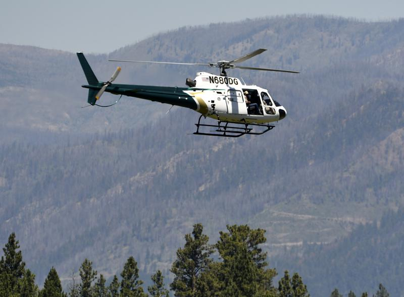 A helicopter from Montana Fish, Wildlife and Parks flies around the Ovando, Mont., area on Tuesday, July 6, 2201, in search of a bear that killed a camper early that morning. The search for the bear continued Wednesday. (Tom Bauer/The Missoulian via AP)