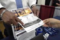Curtis McCray, a Mississippi Department of Corrections recruiter, left, points out a positive testimonial to a job applicant during the Lee County Area Job Fair in Tupelo, Miss., Tuesday, Oct. 12, 2021. Employers representing a variety of manufacturing, production, service industry, medical and clerical companies attended the day long affair with an eye towards recruitment, hiring, training and retention. (AP Photo/Rogelio V. Solis)