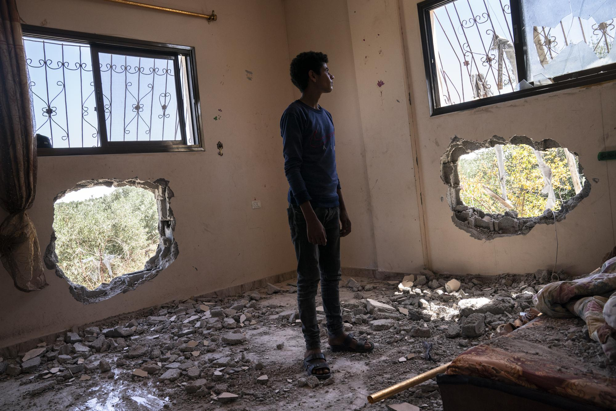 Issat Al-Masri, 18, stands for a portrait in his bedroom that was damaged by shelling prior to a cease-fire that halted an 11-day war between Gaza's Hamas rulers and Israel, Wednesday, May 26, 2021, in Beit Hanoun, Gaza Strip. (AP Photo/John Minchillo)