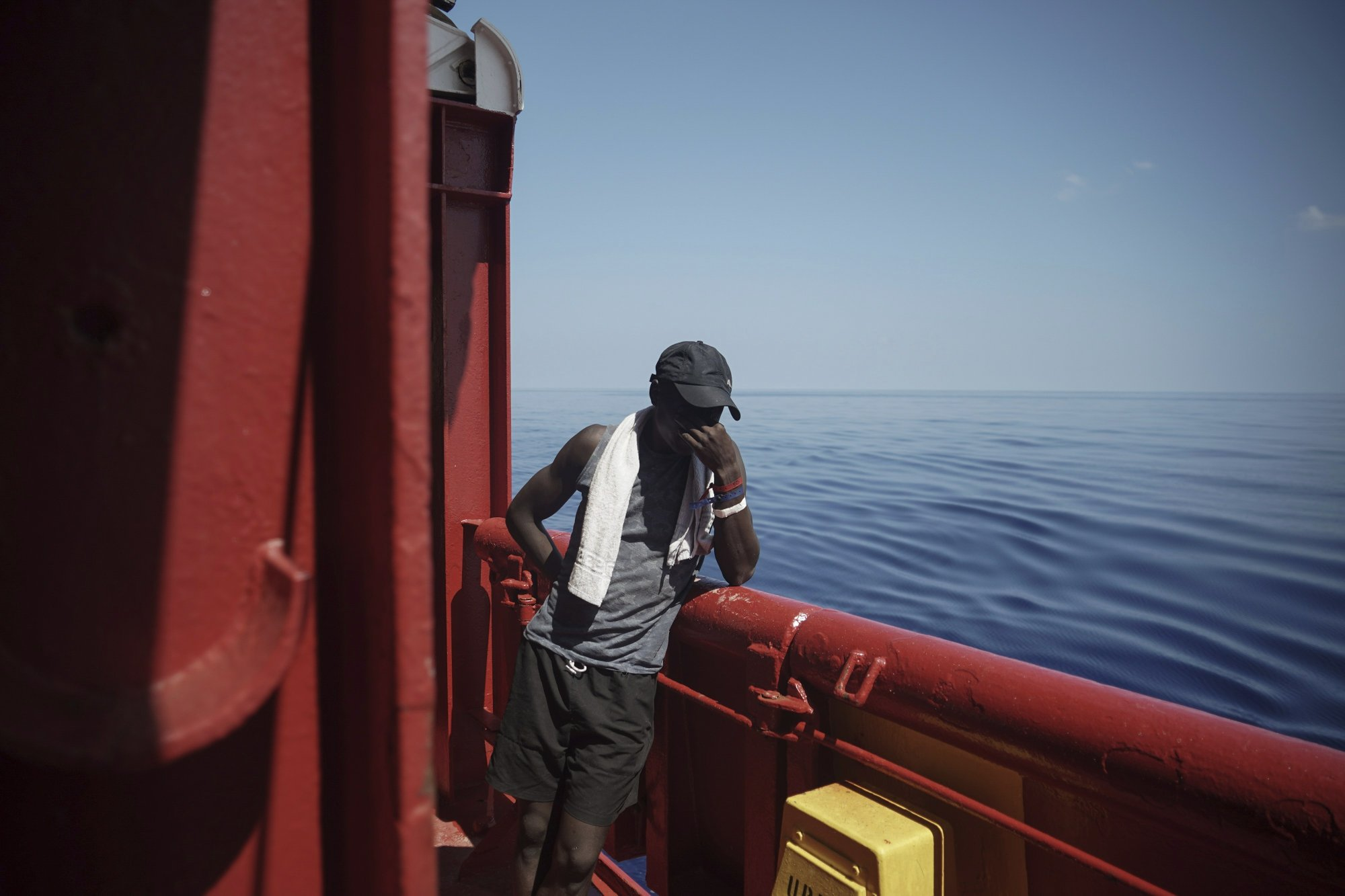 In this Sept. 14, 2019 photo, Amidou from Cameroon touches his face aboard the Ocean Viking humanitarian ship as it sails to Italy in Mediterranean Sea. He was rescued from an overcrowded rubber boat north of Libya as he tried to cross to Europe. While in Libya he spent five weeks in various parts of the Zawiya detention center where he says he was forced to unearth weapons in the desert. (AP Photo/Renata Brito)
