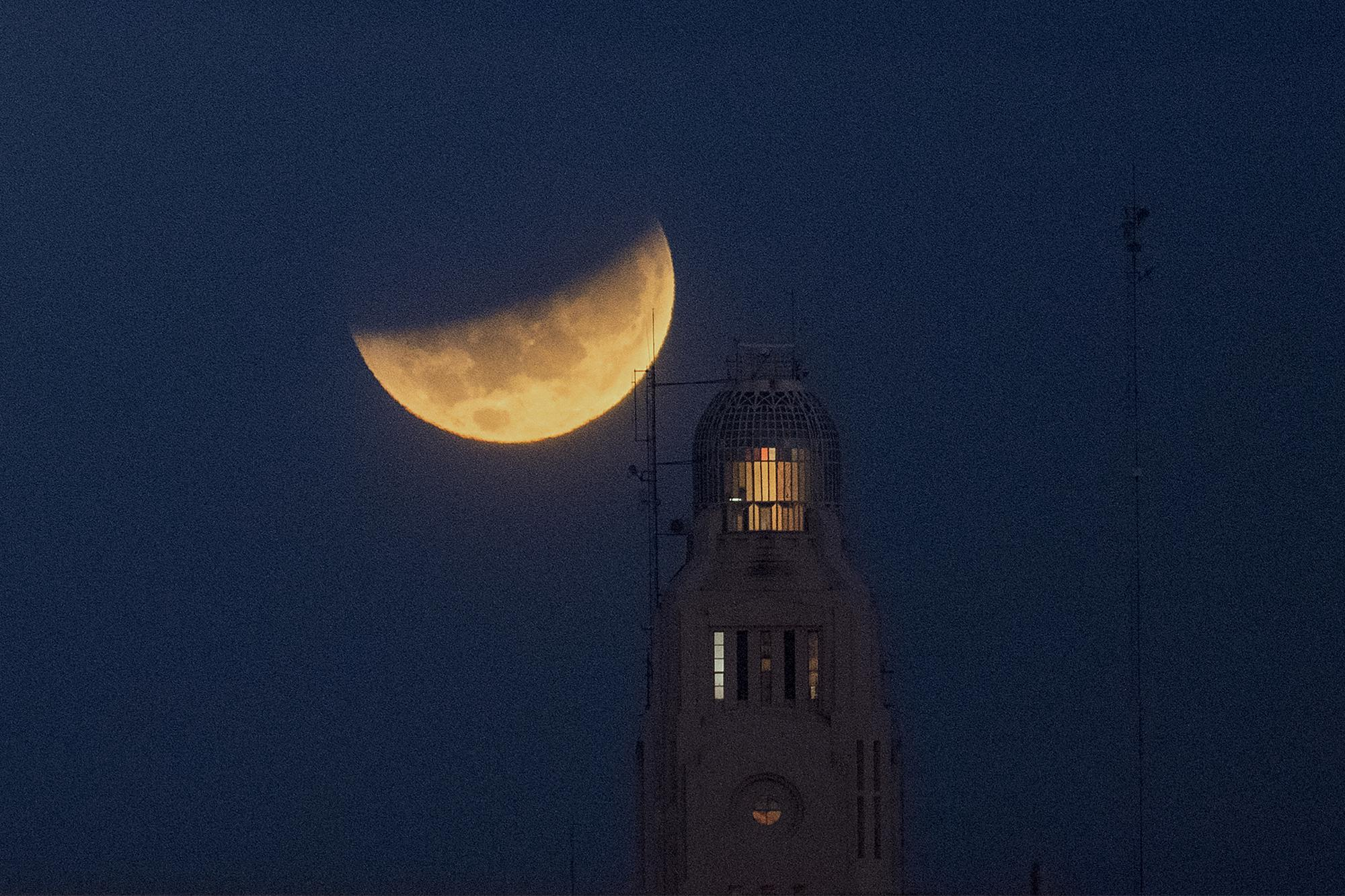 The moon sets behind the Montevideo port, in Uruguay, Wednesday, May 26, 2021, during a lunar eclipse, also known as a super blood moon. (AP Photo/Matilde Campodonico)