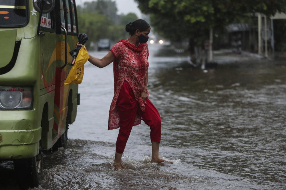 A woman alights from a bus at a flooded street during monsoon rains Jammu, India, Monday, July 12, 2021. India's monsoon season runs from June to September.