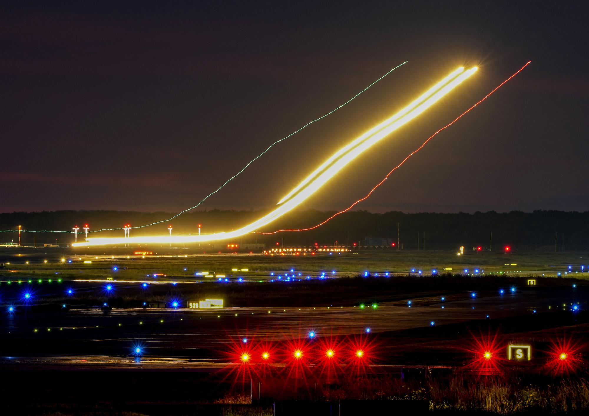 A long camera exposure photo shows an aircraft approaching for landing at the international airport in Frankfurt, Germany, on Monday, Aug. 9, 2021. (AP Photo/Michael Probst)