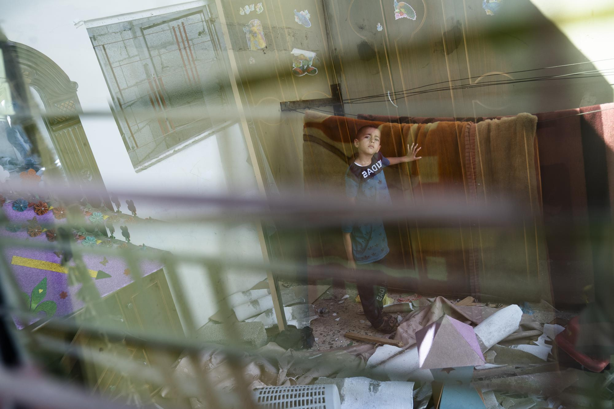 Anas Alhaj Ahmed, 4, stands for a portrait in his bedroom that was damaged when an airstrike destroyed a nearby building prior to a cease-fire that halted an 11-day war between Gaza's Hamas rulers and Israel, Thursday, May 27, 2021, in Maghazi, Gaza Strip. (AP Photo/John Minchillo)