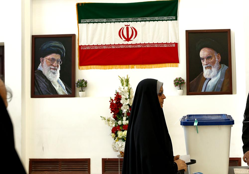 A woman casts her vote during the presidential election at a polling station inside the Iranian consulate in Karbala, Iraq, Friday, June 18, 2021. Iran began voting Friday in a presidential election tipped in the favor of a hard-line protege of Supreme Leader Ayatollah Ali Khamenei, fueling public apathy and sparking calls for a boycott in the Islamic Republic.  (AP Photo/Hadi Mizban)