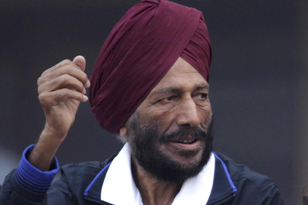 In this Dec. 15, 2013, file photo, former Indian athlete Milkha Singh, with, and Bollywood actor Bipasha Basu waves to the participants during the Delhi Half Marathon in New Delhi, India. Milkha Singh, one of India's first sport superstars and ace sprinter who overcame fought a childhood tragedy and became the country's most celebrated athlete, has died. He was 91.