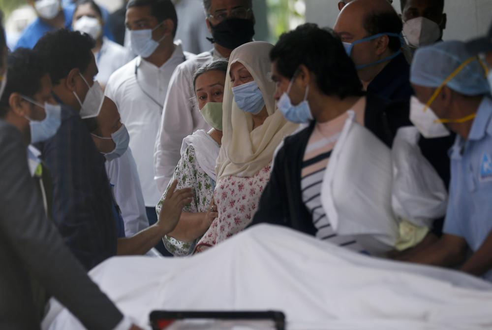 """Saira Banu, wife of Indian actor Dilip Kumar, wearing blue mask, center, mourns near his body at a hospital in Mumbai, India, Wednesday, July 7, 2021. Bollywood icon Dilip Kumar, hailed as the """"Tragedy King"""" and one of Hindi cinema's greatest actors, died Wednesday in a Mumbai hospital after a prolonged illness. He was 98."""