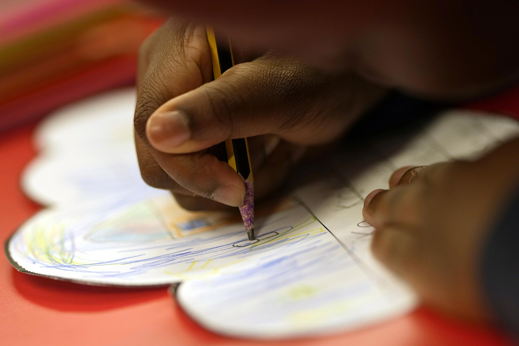 A pupil writes with a pencil during a lesson at the Holy Family Catholic Primary School in Greenwich in London, Monday, May 24, 2021. Holy Family, like schools across Britain, is racing to offset the disruption caused by COVID-19, which has hit kids from low-income and ethnic minority families hardest. (AP Photo/Alastair Grant)