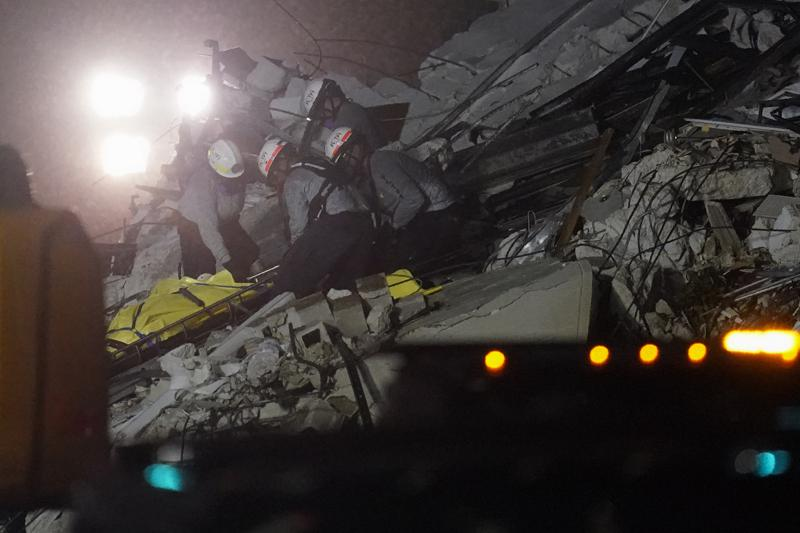 Rescue workers remove a body from the rubble where a wing of a 12-story beachfront condo building collapsed, Thursday, June 24, 2021, in the Surfside area of Miami.(AP Photo/Gerald Herbert)