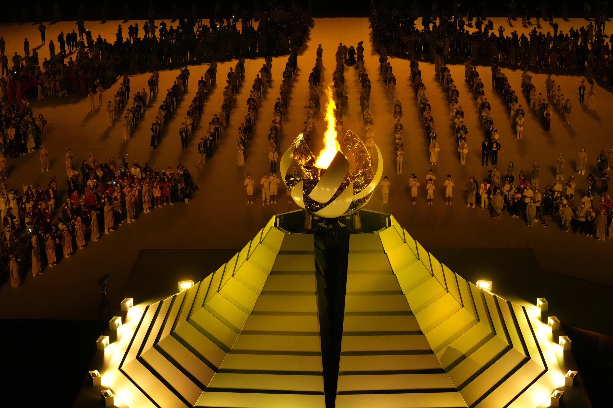 The Olympic flame burns during the opening ceremony in the Olympic Stadium at the 2020 Summer Olympics, Friday, July 23, 2021, in Tokyo, Japan. (AP Photo/Lee Jin-man)