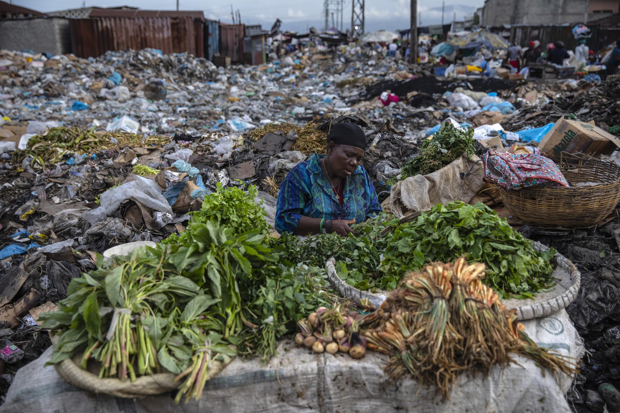 A woman selling greens waits for customers in the Croix des Bosalles market in Port-au-Prince, Haiti, Wednesday, Sept. 22, 2021. The floor of the market is thick with decomposing trash and, in some places, small fires of burning trash. (AP Photo/Rodrigo Abd)