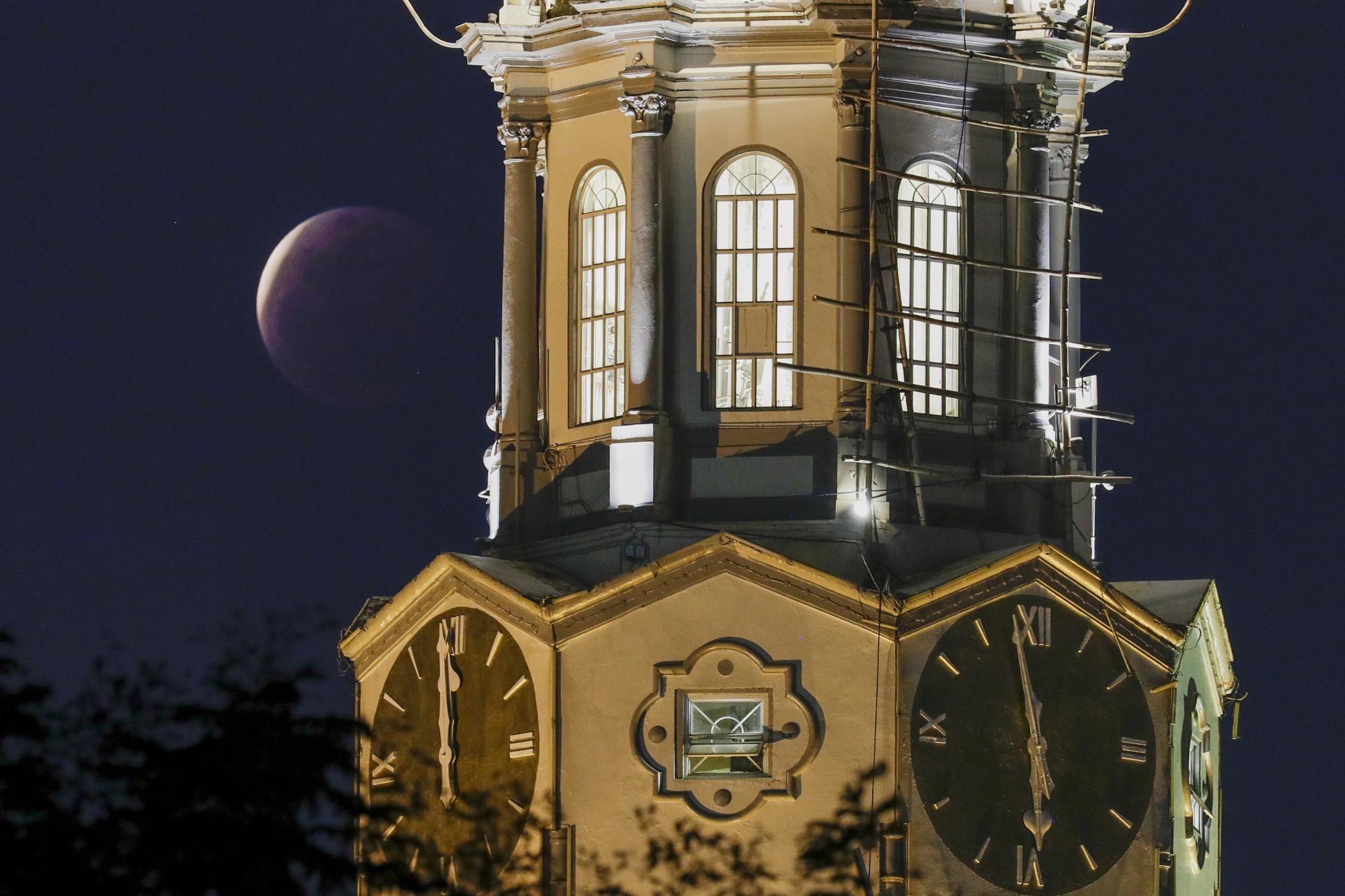 A lunar eclipse occurs beside the clock tower of the Manila City Hall, Philippines, Wednesday, May 26, 2021.  (AP Photo/Aaron Favila)