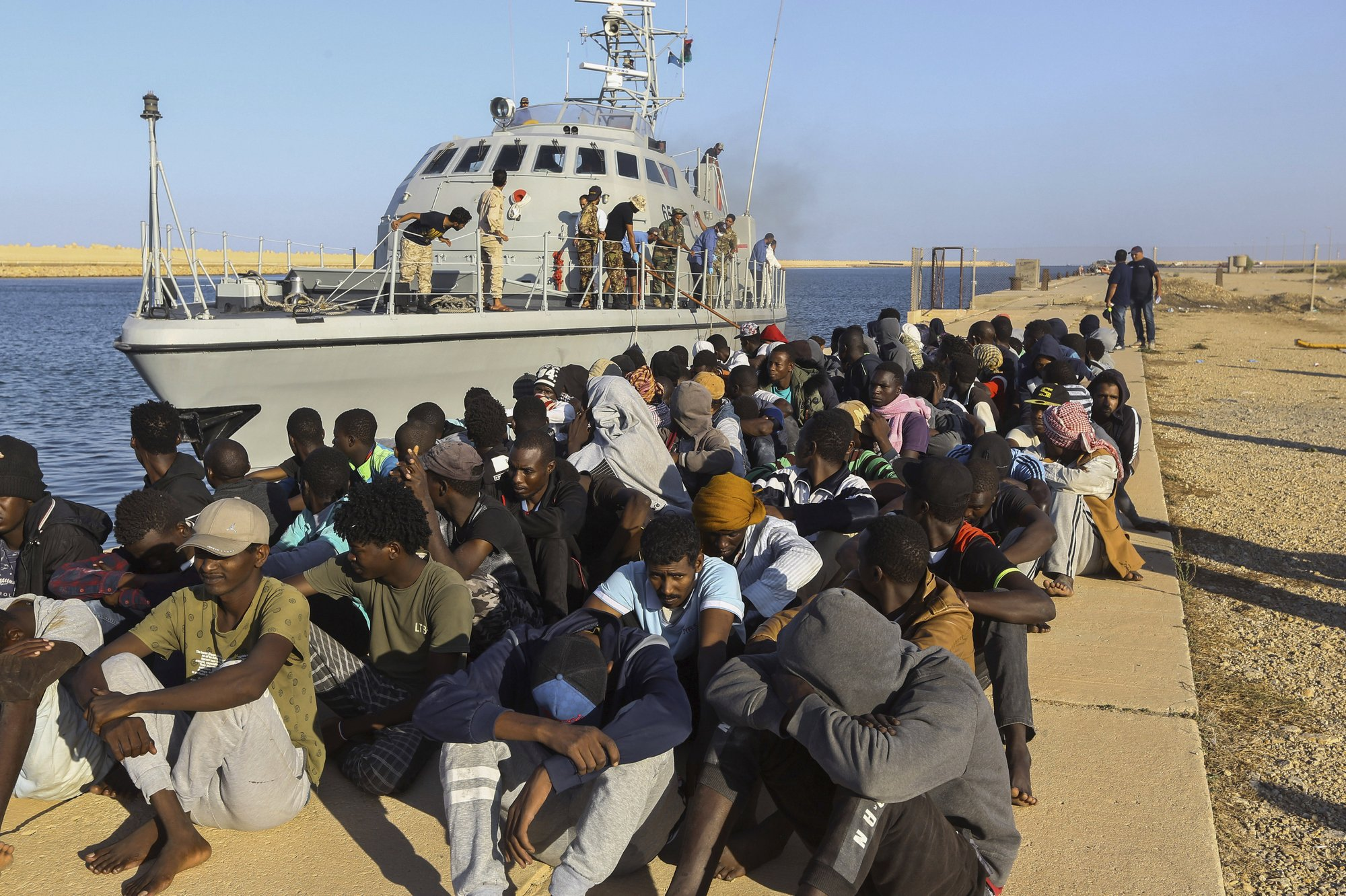 FILE - In this Tuesday, Oct. 1, 2019 file photo, rescued migrants are seated next to a coast guard boat in the city of Khoms, Libya, around 120 kilometers (75 miles) east of Tripoli. When millions of euros started flowing from the European Union into Libya to slow the tide of migrants crossing the Mediterranean, the money came with EU promises to improve detention centers notorious for abuse and to stop human trafficking. That hasn't happened. (AP Photo/Hazem Ahmed,File)