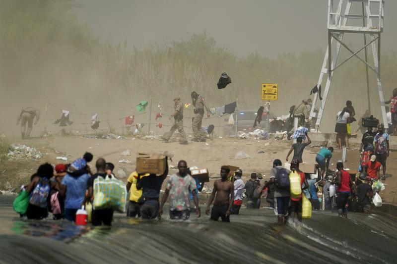 A dust storm moves across the area as Haitian migrants use a dam to cross into and from the United States from Mexico, Saturday, Sept. 18, 2021, in Del Rio, Texas. The U.S. plans to speed up its efforts to expel Haitian migrants on flights to their Caribbean homeland, officials said Saturday as agents poured into a Texas border city where thousands of Haitians have gathered after suddenly crossing into the U.S. from Mexico. (AP Photo/Eric Gay)