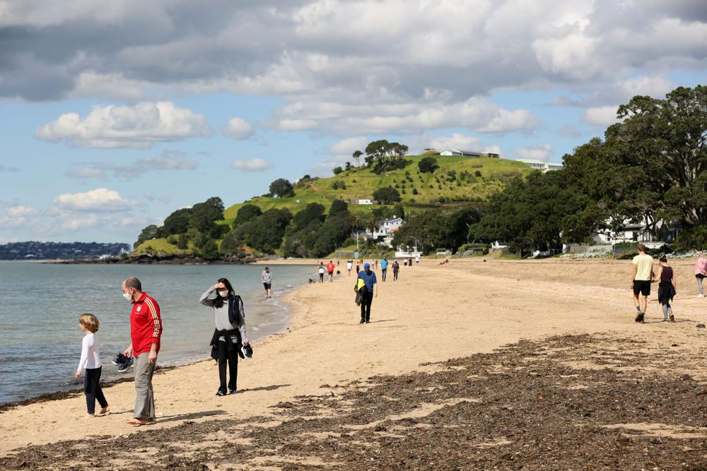 People walk on the beach in Auckland, New Zealand, Thursday, Sept. 2, 2021. The southern winter that just ended in New Zealand was the warmest ever recorded, and scientists say that climate change is driving temperatures ever higher. (Sylvie Whinray/New Zealand Herald via AP)