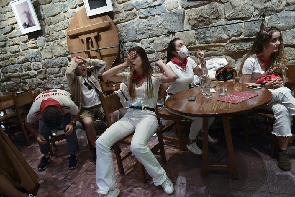 Spanish fans react after their team lost against Italy while watching the televised Euro 2020 soccer championship semifinal match at a bar in Pamplona, northern Spain, Tuesday, July 6, 2021. (AP Photo/Alvaro Barrientos)
