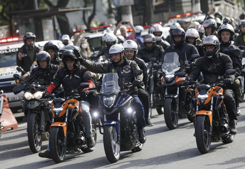 Brazil's President Jair Bolsonaro, center, waves as he leads a caravan of motorcycle enthusiasts following him through the streets of the city, in a show of support for Bolsonaro, in Sao Paulo, Brazil, Saturday, June 12, 2021. (AP Photo/Marcelo Chello)