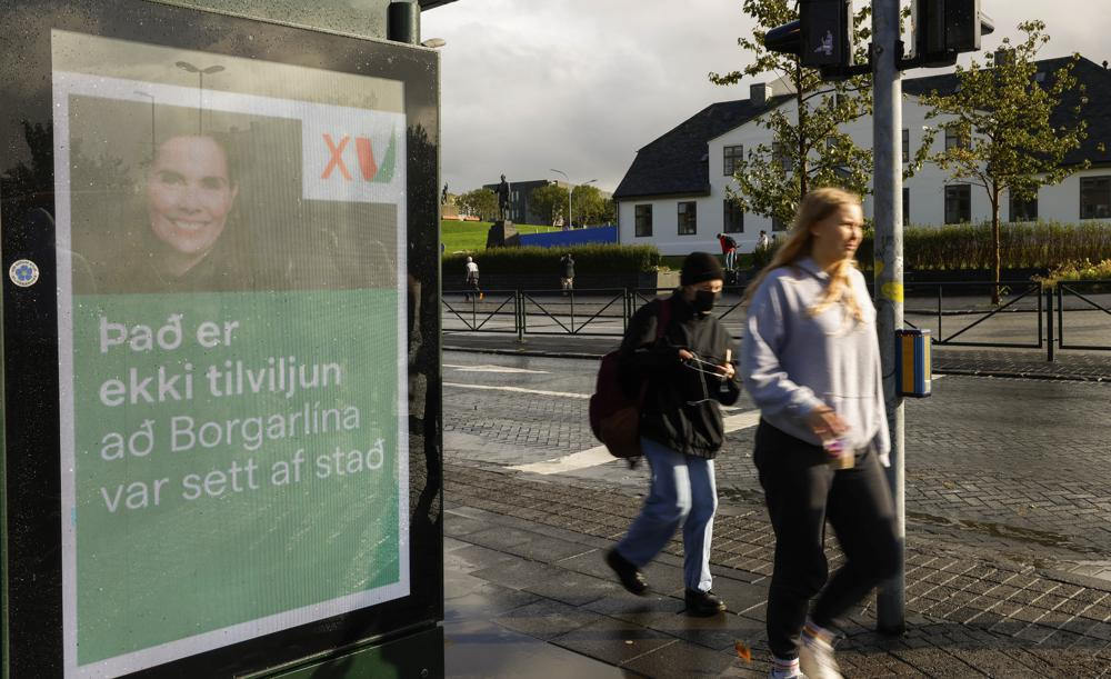 """People walk past an election poster from the Left Green Party, showing Prime Minister Katrin Jakobsdottir and saying """"It isn't coincidence that the City Lane was launched"""" in Reykjavik, Iceland, Wednesday, Sept. 22, 2021. Climate change is top of the agenda when voters in Iceland head to the polls for general elections on Saturday, following an exceptionally warm summer and an election campaign defined by a wide-reaching debate on global warming. Polls suggest Prime Minister Katrin Jakobsdottir's Left Green Party could face a poor outcome, ending the current coalition. (AP Photo/Brynjar Gunnarsson)"""