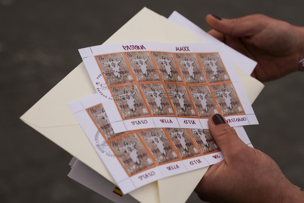 La artista Alessia Babrow muestra los sellos del Vaticano durante una entrevista con Associated Press, en el Vaticano, el viernes 14 de mayo de 2021. Babrow demandó a la oficina de telecomunicaciones del Estado de la Ciudad del Vaticano en un tribunal de Roma el mes pasado, diciendo que se estaba aprovechando injustamente de su creatividad y violando la intención original de su obra de arte.  La demanda, que busca casi 130.000 euros en daños y perjuicios, dijo que el Vaticano había ignorado los intentos de Babrow de negociar un acuerdo después de que descubrió que había reproducido ilegalmente el arte de su cartel.  (Foto AP / Andrew Medichini)